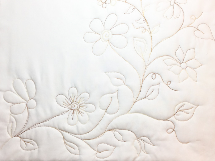 An improvisational free motion quilting design with leaves and flowers waiting for color