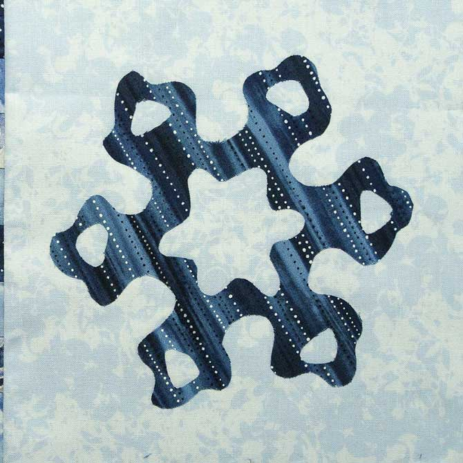 Snowflake fused to light hued background fabric