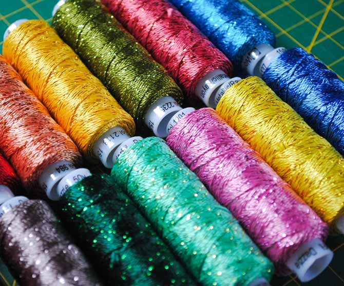 A rainbow of Dazzle threads from WonderFil are arranged on a cutting board.