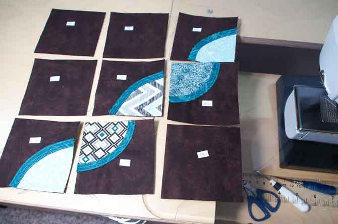 9 patch block laid out in order at sewing machine ready to sew together
