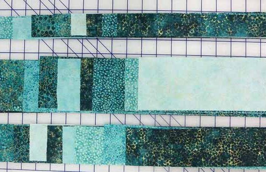"""Fabric strips 1½"""", 2½"""" and 3½"""" wide cut from Northcott's Artisan Spirit Shimmer and Echoes fabrics in the Peacock colorway."""