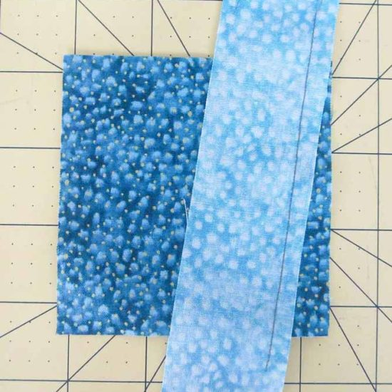 Sew the first strip of Artisan Spirit fabric to the center square on an angle.