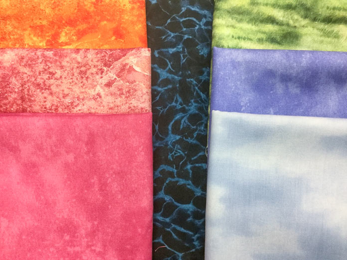 A selection of fabrics from Northcott including a light blue sky print, green grass print, a coral pink, a periwinkle blue, an orange ombre, a coral ombre and a dark blue crackle print  Northcott