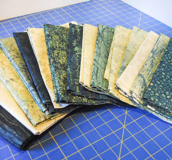 A selection of Northcott's Stonehenge Elements fabrics fanned out on the cutting table