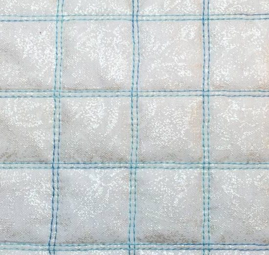 A checkerboard grid is created by stitching evenly spaced horizontal and vertical rows. The twin needle adds charming detail that would be difficult to obtain if we were using a single needle. SCHMETZ / H.A. KIDD