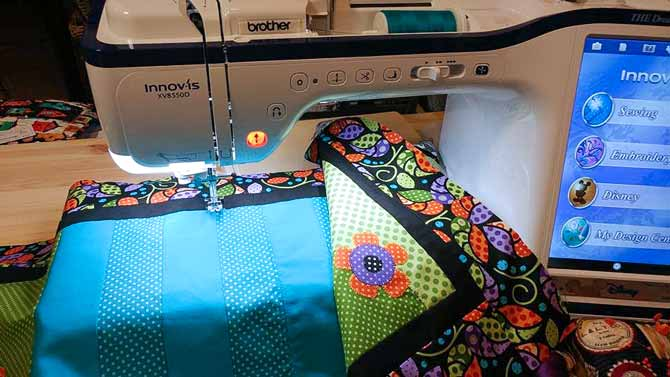 My table runner is back under my needle as I get ready to continue the faux applique stitch along another of the pieced seams