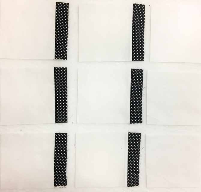 Nine white squares of fabric on the design wall, with six black sashing strips sewn to the right hand side of six of the squares