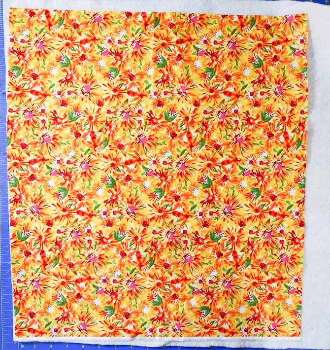 floral print in yellow, green and red on a piece of batting and blue cutting mat