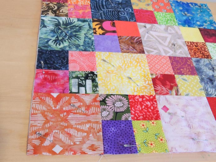 Patchwork panel layered and pinned for quilting