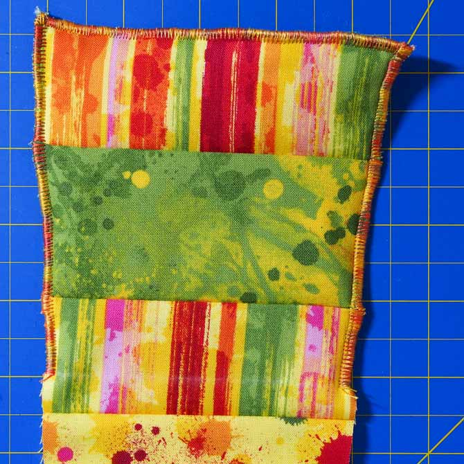 Zigzag stitch done on back multicolored piece in orange thread