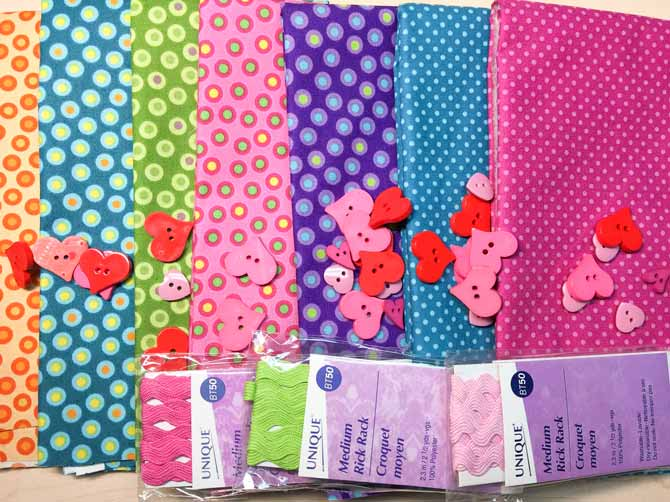 Multi colored polka dot fabric pieces with heart buttons and bundles of rick rack.