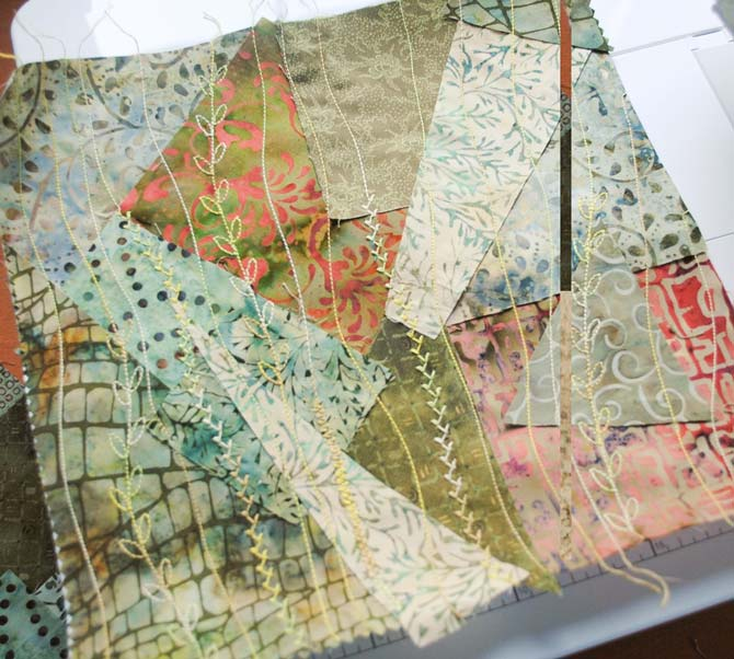 A crazy quilt base made with green fabrics, lightweight interfacing and Fruitti thread from WonderFil.