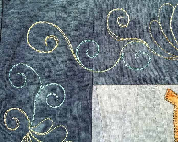 Corner detail of Be Curious quilted with WonderFil Accent thread