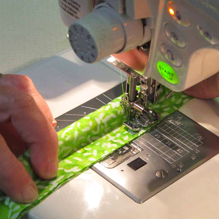 Use a zipper foot to stitch close to the cording.
