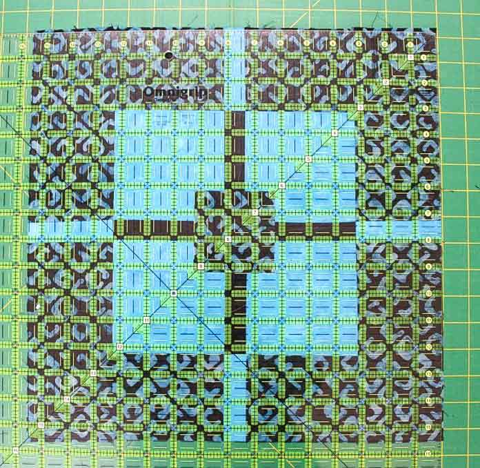 One of Claire Haillot's many tips for accomplishing the Deep Waters Quilt, which looks complex but is actually very easy to make. See what too look for on the Omnigrid ruler when squaring off your quilt blocks...