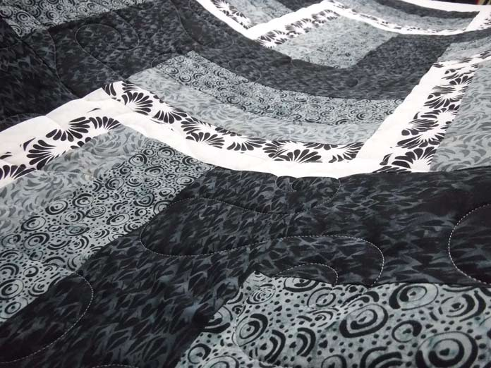 Curvy, fluid quilting designs soften the linear peicing. The quilting is spread further apart to showcase the beautiful fabrics from the NEW Banyan Batiks Banyan Classics Collections. Free rail fence quil