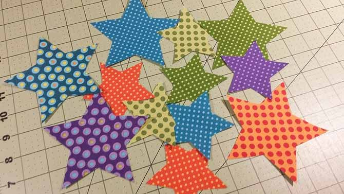 The 12 star applique shapes made from Northcott Fabric's Urban Elementz Basix Collection; 5 large and 7 small stars will be used to make Bill's All Stars Table Topper.