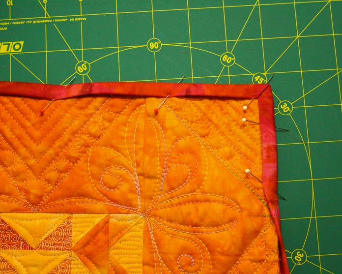 Bring binding to front side of quilt and pin.