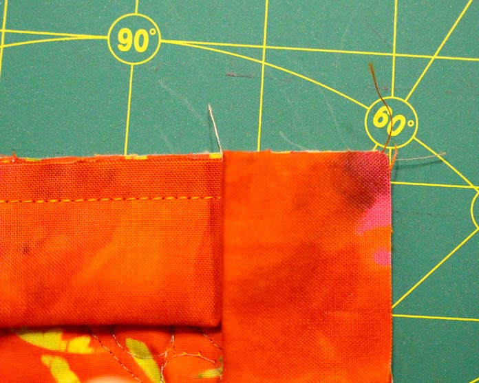 Fold binding down even with the edge of the quilt.