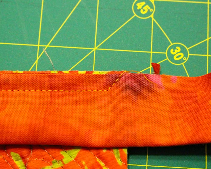 Sew binding to the edge of the quilt and stitch out to the corner.