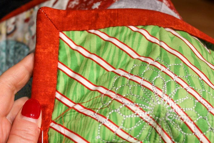 Hand stitch the folded edge of the binding to the back of the quilt.