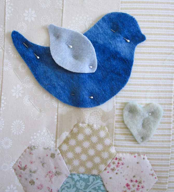 Little bird pinned to the studio mini wall quilt. WonderFil Specialty Threads.