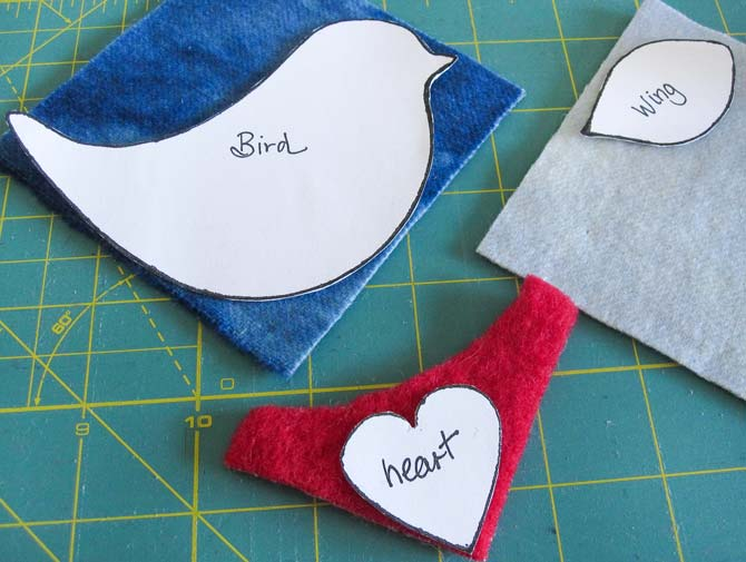 Templates of a bird shape, wing shape, and heart shape placed on wool pieces arranged on a cutting board. WonderFil Specialty Threads.