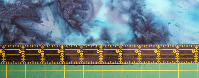 """Use the 1"""" x 12"""" ruler and slide it along the seam and cut off any excess fabric for accurate piecing."""
