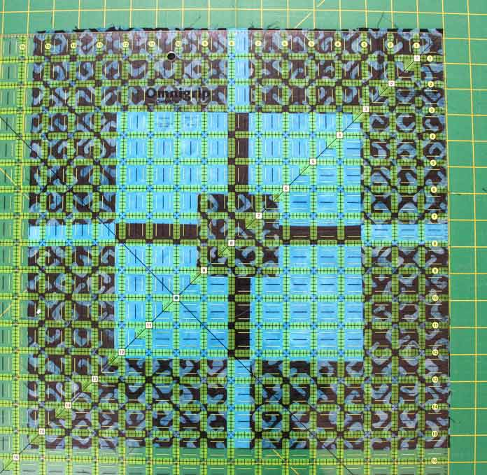 Before cutting off any excess fabric, I ensure that my vertical and horizontal lines align with my center strip. I also ensure that my diagonal is aligned with the corners of my squares, Only when they all match, I cut off excess fabric... if any.