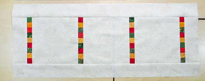 Cream fabric with strips of gold/red/green squares between the cream fabric to create a Christmas runner