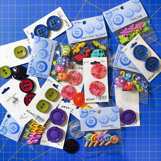 multiple buttons in varied colours and designs on a blue cutting mat
