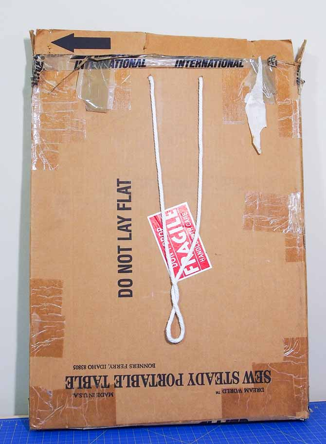 A cardboard box with rope handles leaning against a wall and sitting on a blue cutting mat