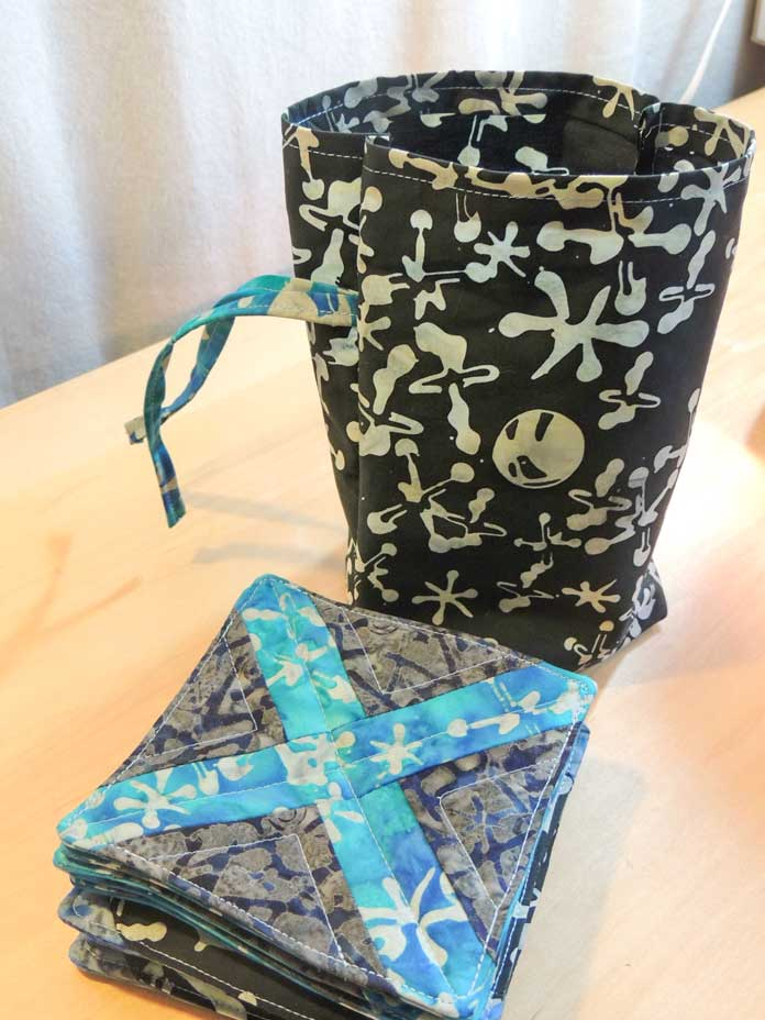 Carrying bag beside quilted game pieces