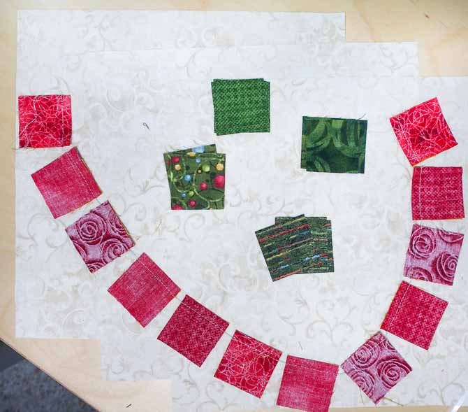 Red squares lying on cream fabric in a chain and green squares sitting above them