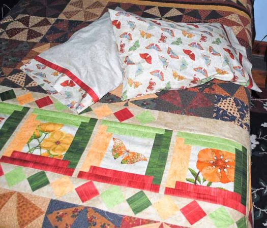 Completed pillowcases using elegant French seams and trim, along with the Log Cabin pattern bed runner top using Northcott Euphoria Fabrics