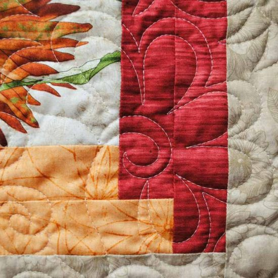A close up of the flower design machine quilted with WonderFil's Master Quilter thread on the bedrunner made with Northcott's Artisan Spirit - Euphoria fabric.