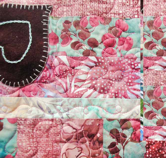 A close up of the heart designs machine quilted on the Valentine's Day tablerunner using WonderFil's Tutti thread.