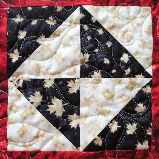 A close up of the leaf design machine quilted on the tablerunner using WonderFil's Master Quilter thread.