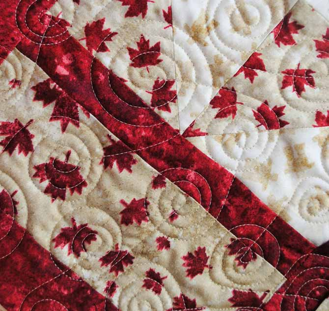 A close up of the spiral design used to machine quilt the Canada Day tablerunner using WOnderFil's Master Quilter thread.