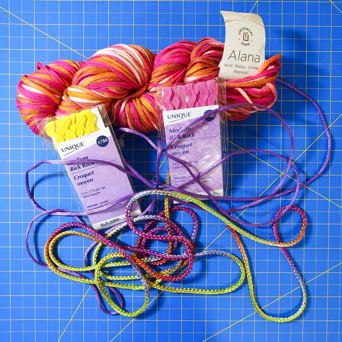 multicolored yarn, rickrack and cording on a blue cutting mat