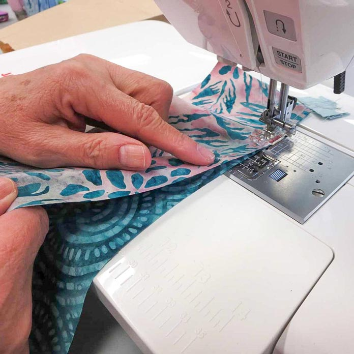Stitch slowly to sew the 2 curved edges together, while slightly lifting the top strip; using Banyan Batiks Island Vibes fabrics.