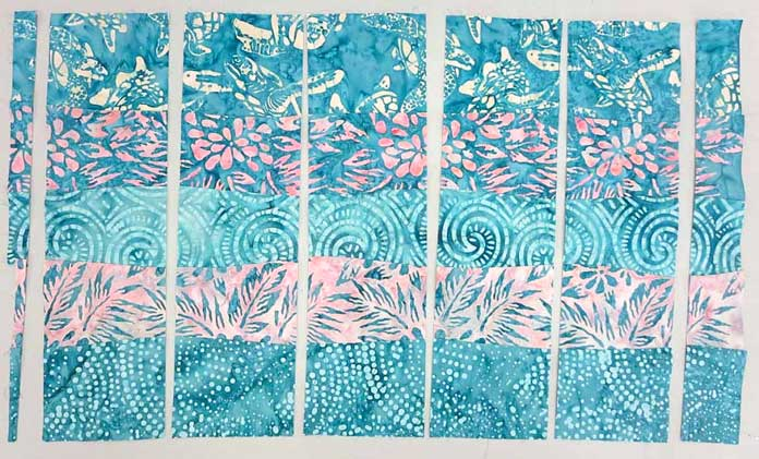 """Use a rotary cutter to cut the strip set into 5 - 4"""" segments; using Banyan Batiks Island Vibes fabrics to make a modern quilt, placemat, cushion cover etc."""