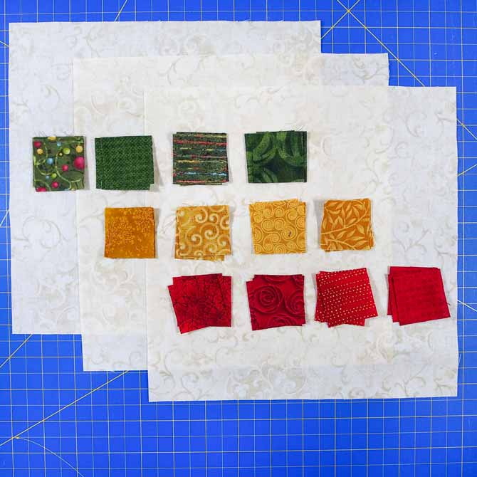 Red, green and gold small fabric squares on larger cream fabrics squares on a blue cutting mat