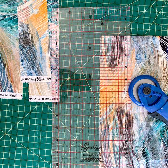 A picture showing a rotary cutter, acrylic ruler, self-healing cutting mat and patterned fabric