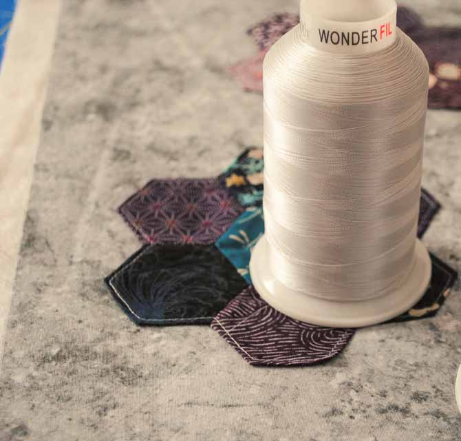 WonderFil's DecoBob thread on a grey hexagon tablerunner.