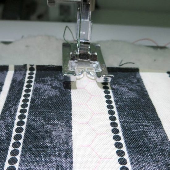 The projector shows the stitch image on the fabric.
