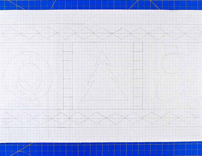 Pencil drawing on graph paper of a Christmas table runner sitting on a blue cutting mat