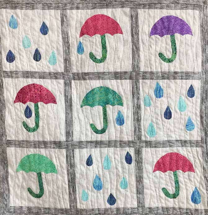 Quilted wall hanging with umbrellas and raindrops using colorful fabric on gray background. Northcott Artisan Spirit Shimmer Echoes fabric.