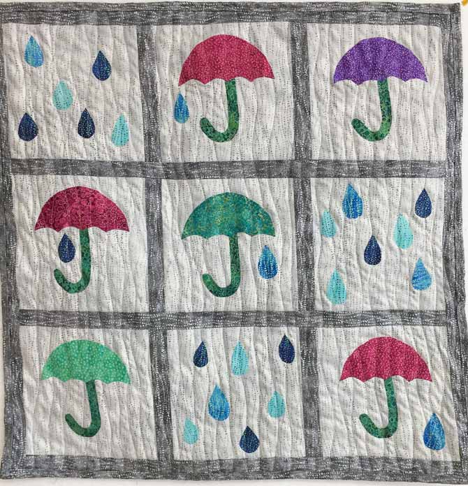 Completed umbrellas and raindrops quilted wall hanging, machine quilted with wavy lines. Northcott's Artisan Spirit Shimmer Echoes.