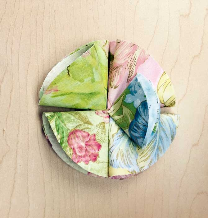 Using the smaller circles, fold and tack onto bottom layer of petals.